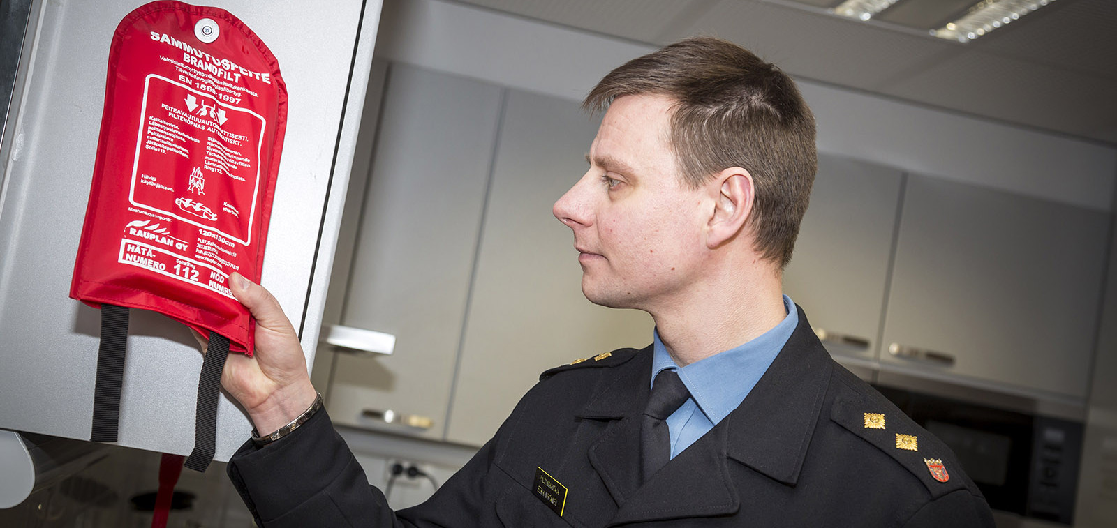 Palotarkastaja katsoo sammutuspeitettä keittiössä