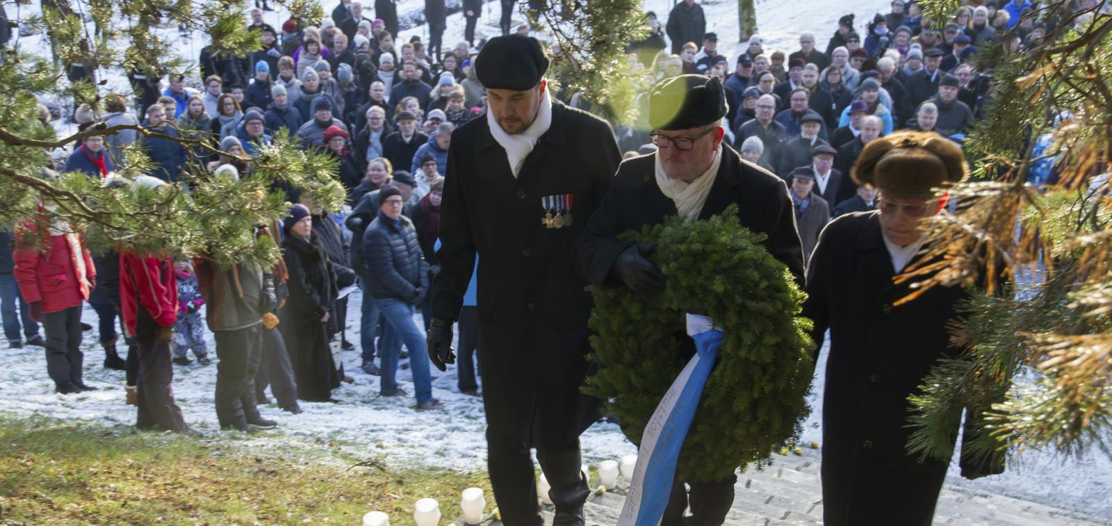 Vakavailmeiset miehet kantavat havuseppelettä Sakariristille suuren yleisön seuraamana