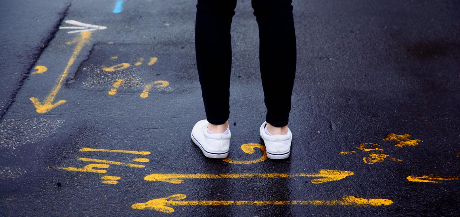 Henkilö seisoo asfaltilla, jossa merkintöjä