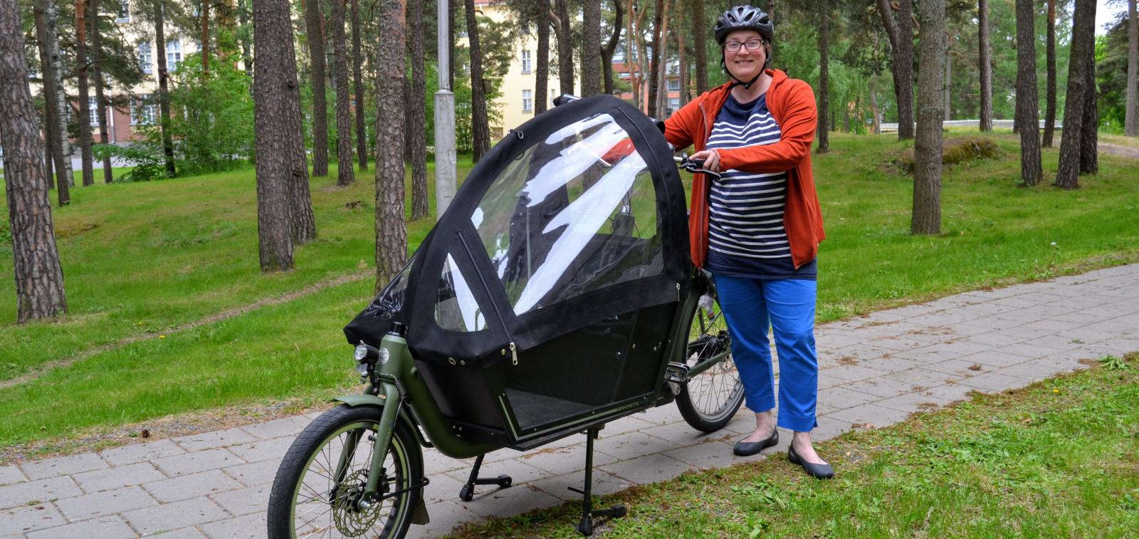 Suvi Vainiomäki ajamassa sähköavusteisella tavarapyörällä työmatkansa.