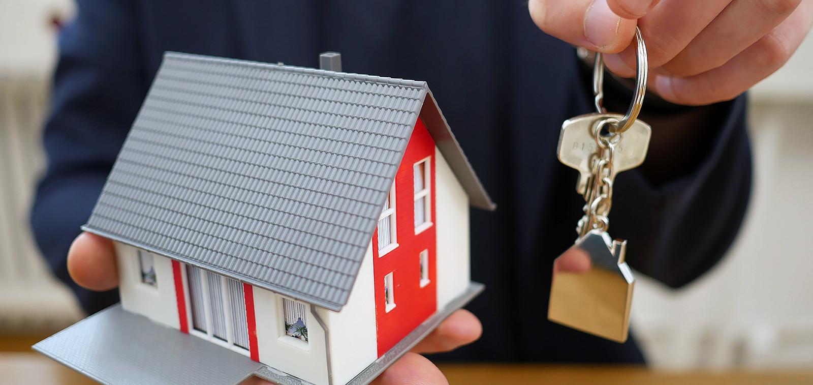 Kädessä talon pienoismalli ja toisessa kädessä avaimet