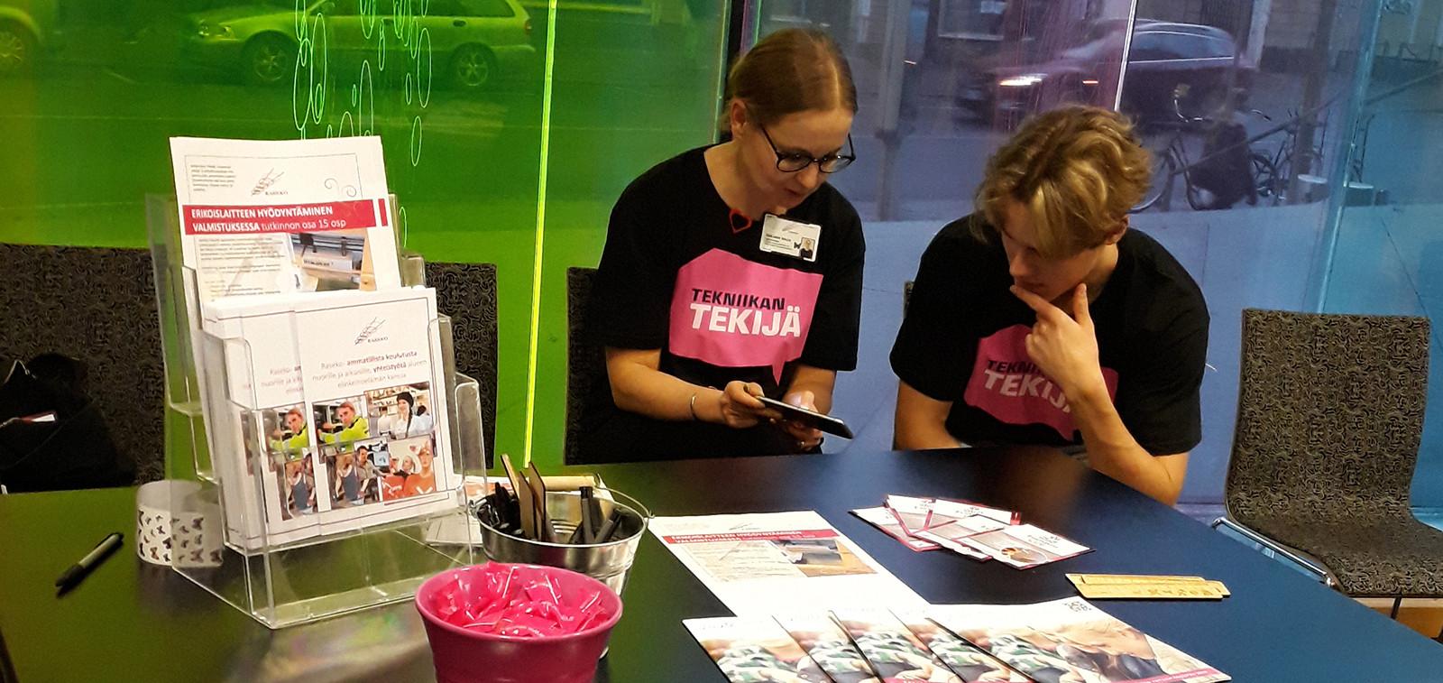 Kuvassa kaksi nuorta kirjastossa Tekniikan taitaja -esittelypisteellä, joista vasemmanpuoleinen nuori näyttää puhelinta oikeanpuoleiselle nuorelle. Pöydällä on tekniikan alojen koulutusesitteitä.