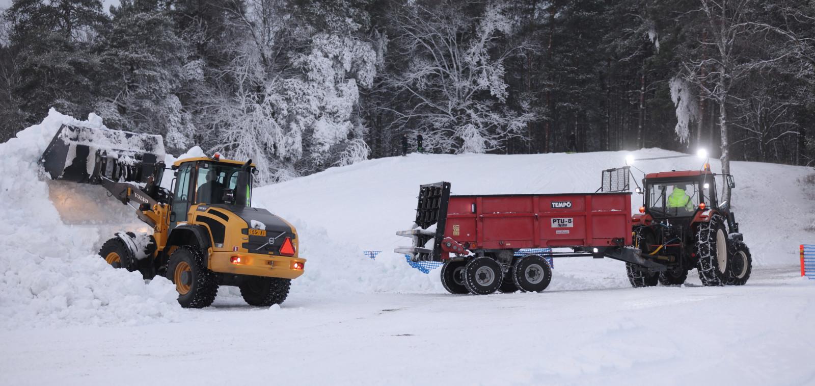 Traktori ja kuorma-auto lumenkuljetuksessa.