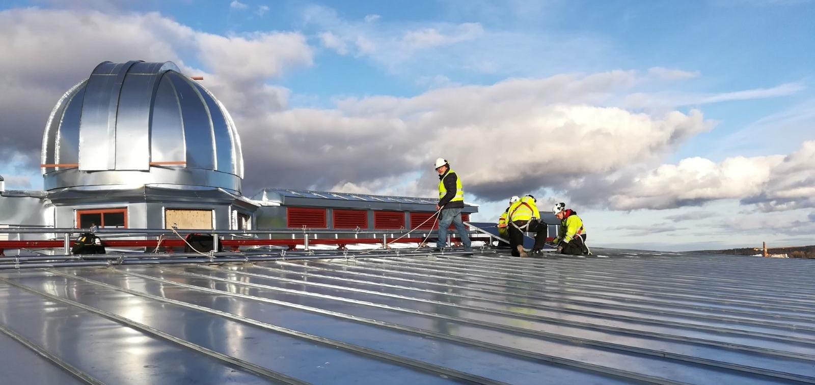 Rakentajat asentavat aurinkopaneelia TSYK:n katolle. Heillä on päällään keltaiset huomioliivit.