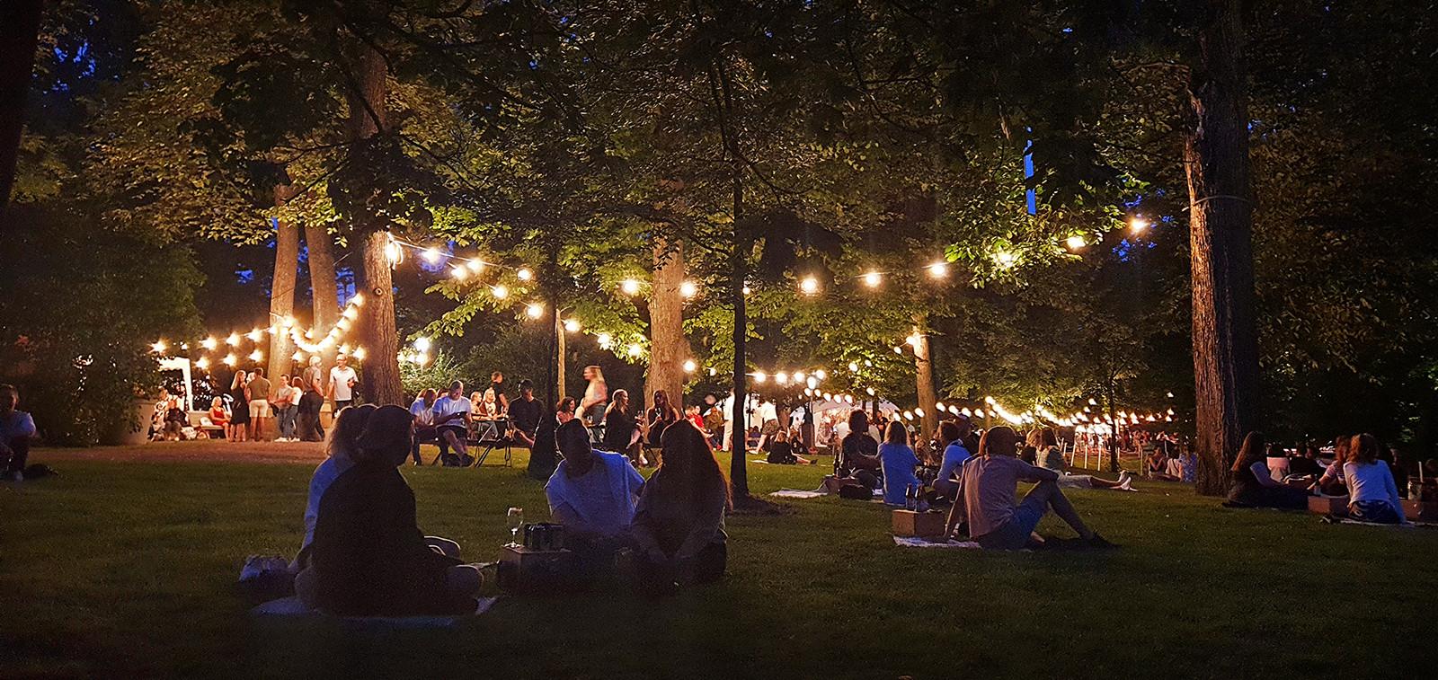 Ihmisiä istuskelemassa iltapimeällä Tuomiokirkon terassin puistossa.