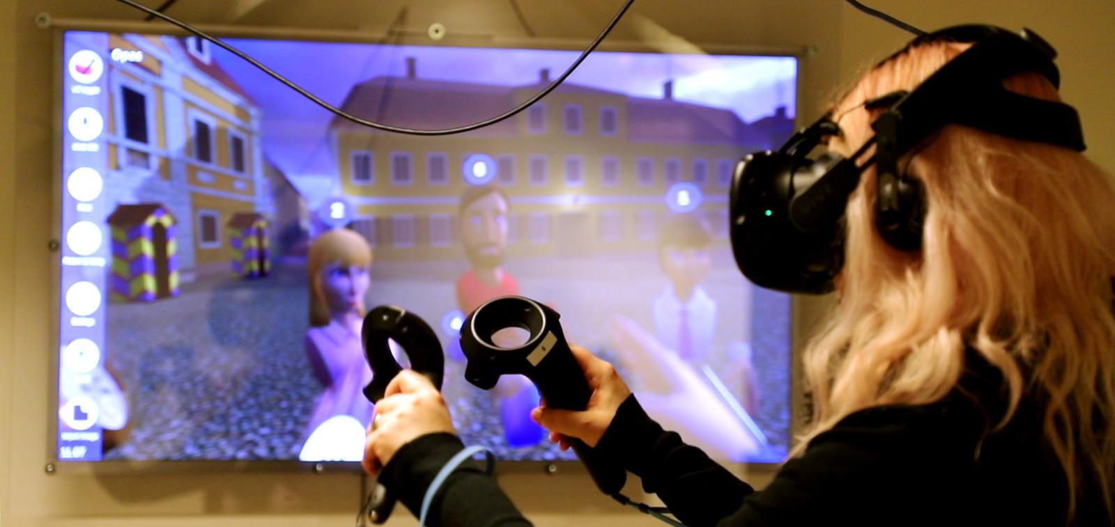 Opas virtuaalilasit päässä, taustalla virtuaalimaailmasta kuva