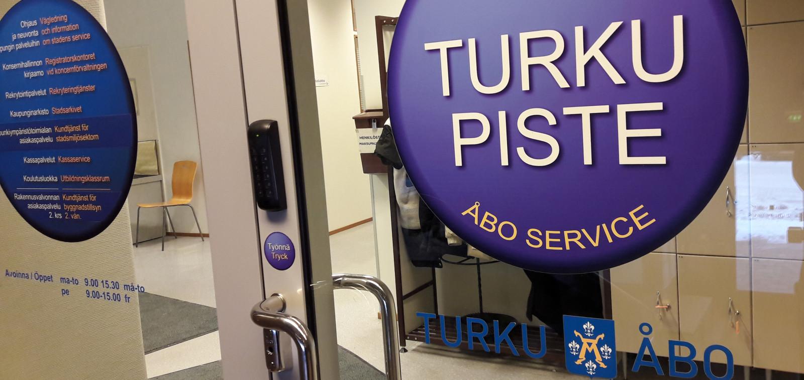Turku-pisteen lasipariovi jossa kaksi isoa sinistä Turku-piste -tarraa