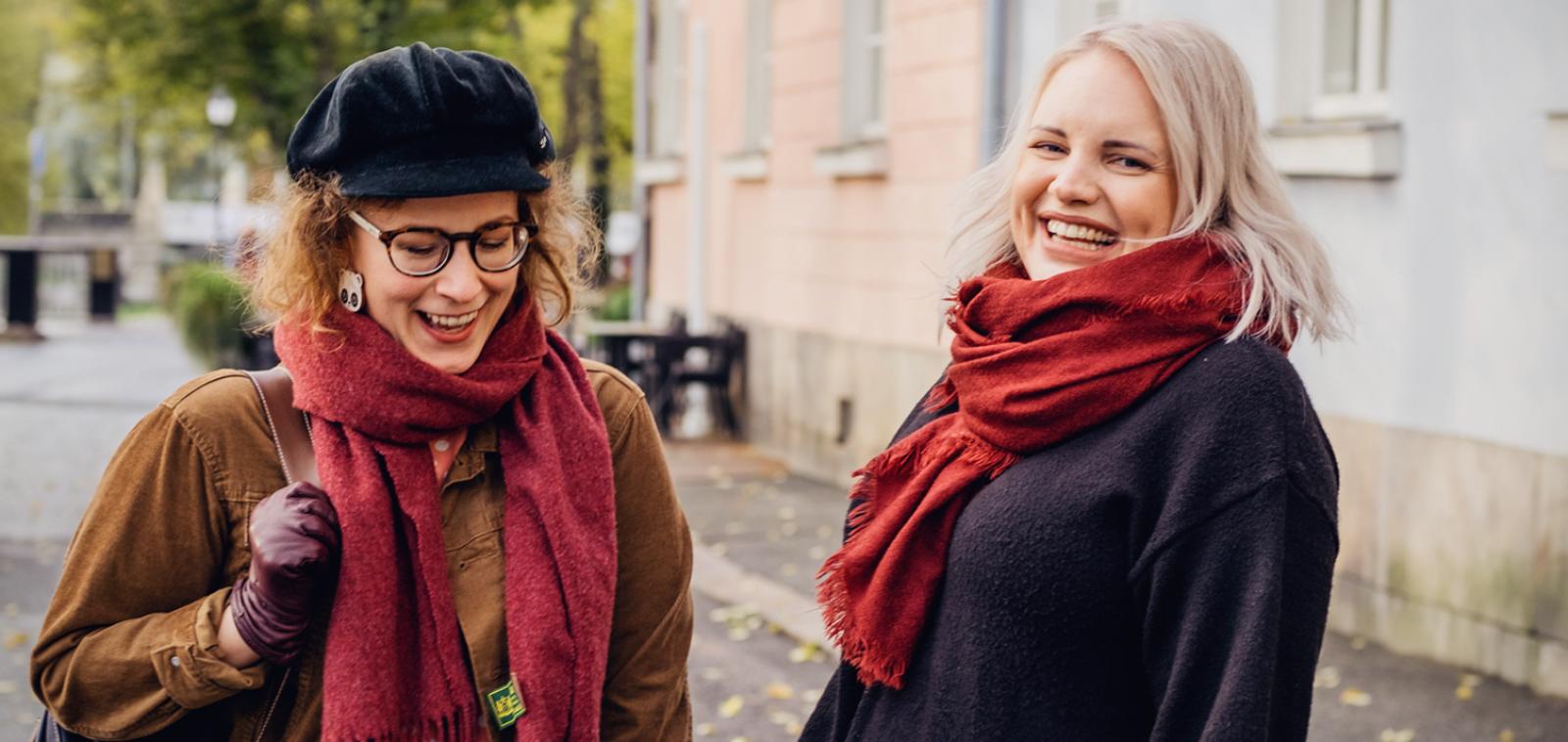 Kaksi naista hymyilee iloisesti.