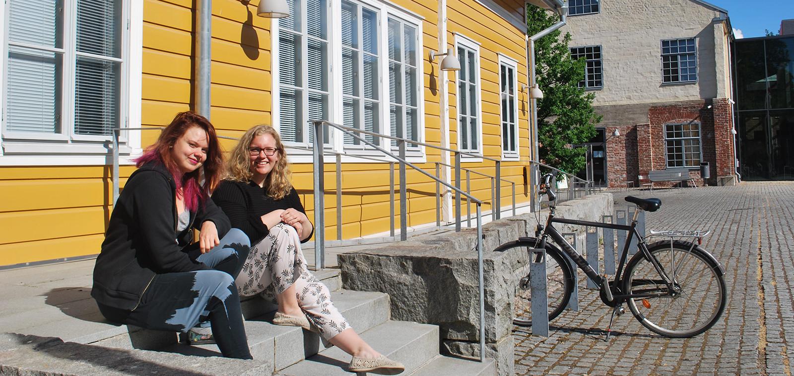 Kaksi opiskelijaa istuu Arkenin ulkopuolella