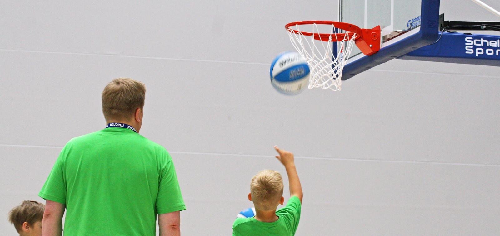 Valmentja ja lapsi koripallokoulussa