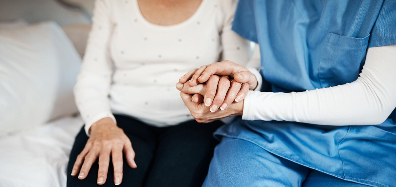 Hoitaja pitää vanhusta kädesta.