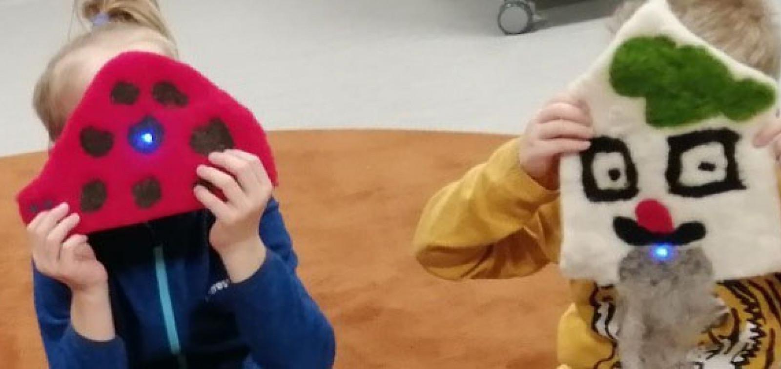 Lapset mukana STEAMit! -kokeilussa. Kaksi lasta pitää kasvoillaan itsetehtyjä huovutettuja voimahahmoja, joissa led-valot.