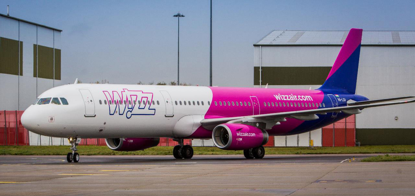 Wizz Air's white, pink and blue covered airplane stands at the airport in front of the airport buildings.