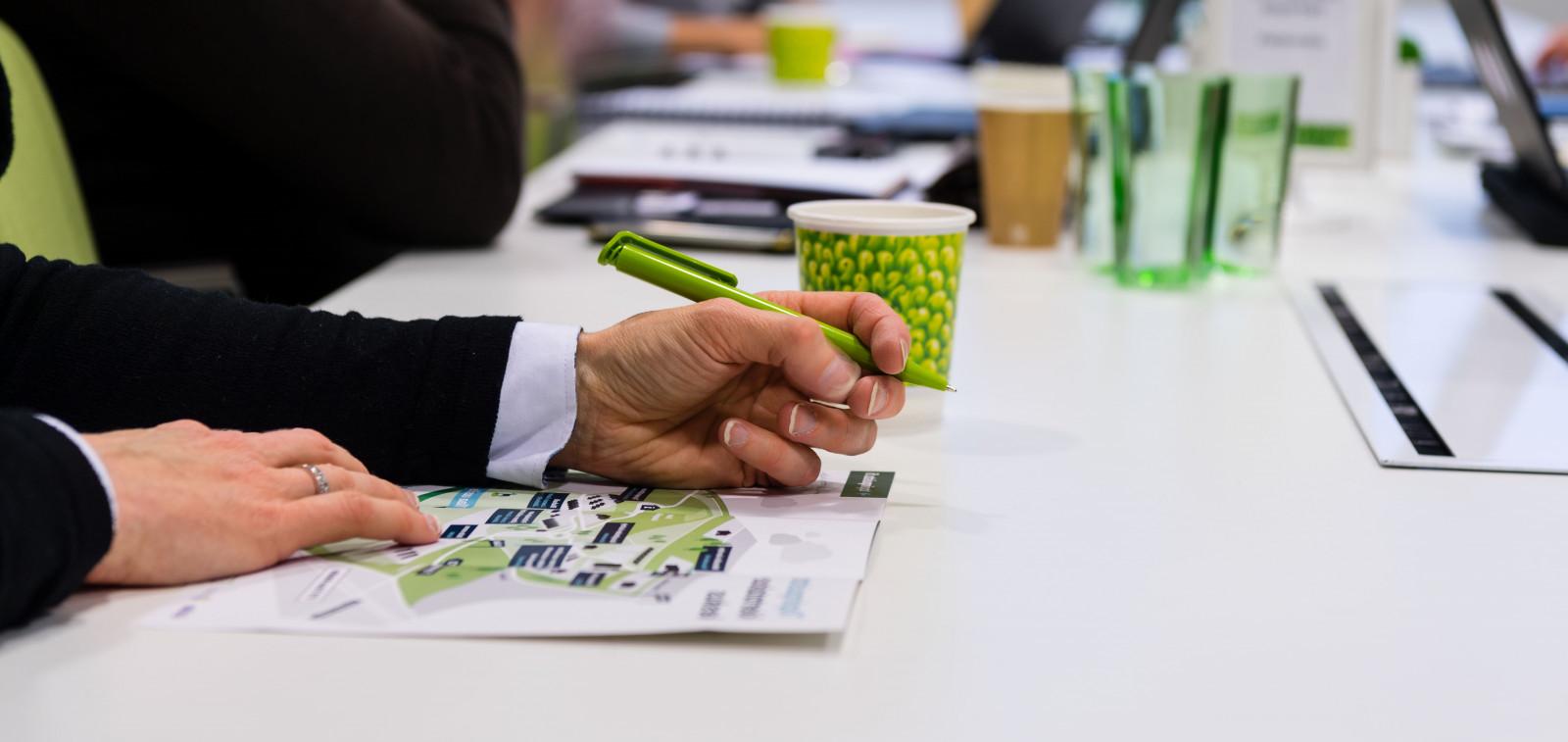 Toimistopöydällä näkyvä käsi, joka pitelee kynää