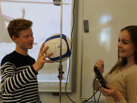 Tyttö ja poika oppitunnilla mittaamassa jalkapallon liikeratoja