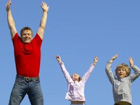 Isä ja lapset hyppivät.