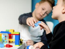 Kaksi poikaa leikkii legoilla, toinen istuu pyörätuolissa.