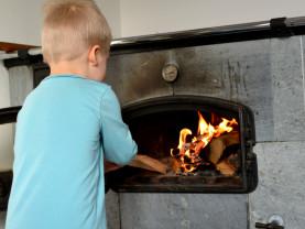 Poika lisää polttopuuta uuniin