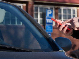 Auto parkissa ja ihmisellä puhelin kädessä