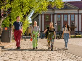 Neljä opiskelijaa kävelee Turun pääkirjaston edustalla.