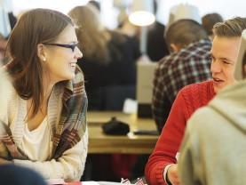Kaksi opiskelijaa keskustelee Turun pääkirjastossa