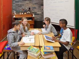 Koululaiset lukevat pulpettien ääressä