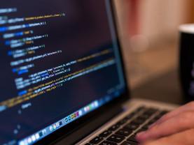 Henkilön kädet kirjoittavat koodia koneella.
