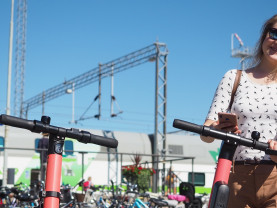 Nainen sähköpotkulautojen kanssa, taustalla polkupyöriä ja juna.