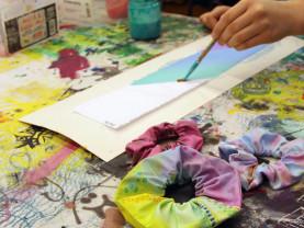 Pöydällä kolme värikästä hiusdonitsia. Käsi, joka maalaa donitsiin tulevaa kangaskaistaletta.