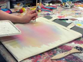 Käsi maalaa siveltimellä kangasta.