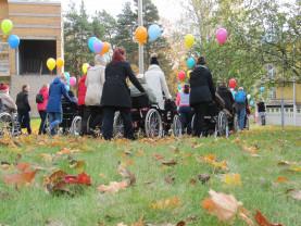 Vapaaehtoiset työntävät Kurjenmäkikodin asukkaita pyörätuoleissa ulkona syyspäivänä