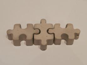 Kolme kolmiulotteista palapelinpalaa yhdessä vaalealla alustalla