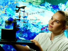 Valkoiseen laboratoriotakkiin pukeutunut oppilas pitelee mekaanista vaakaa, taustalla värikäs mikroskooppikuva.