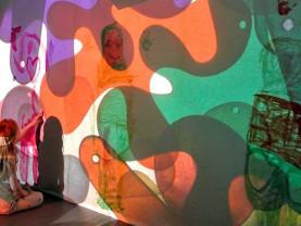 Tyttö istuu ja maalaa seinään, jossa varjokuvia