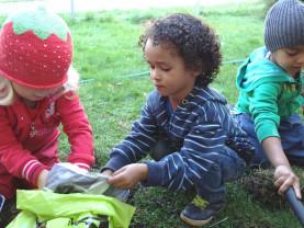 Lapset istuttavat maahan kasveja